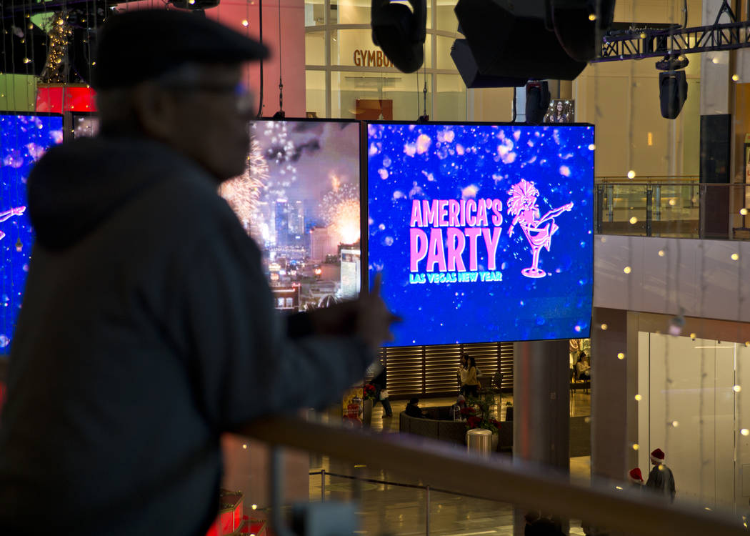 "Osias Belese looks out at display screens before the ""America's Party"" news conference announcing details of Las Vegas New Year's Eve celebrations inside the Great Hall of the Fa ..."
