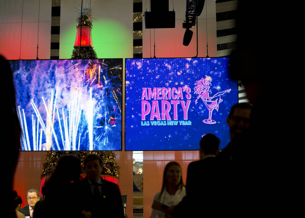 People walk by during the America's Party news conference announcing details of Las Vegas New Year's Eve celebrations inside the Great Hall of the Fashion Show Mall on Thursday, Dec. 21, 2017. Dan ...