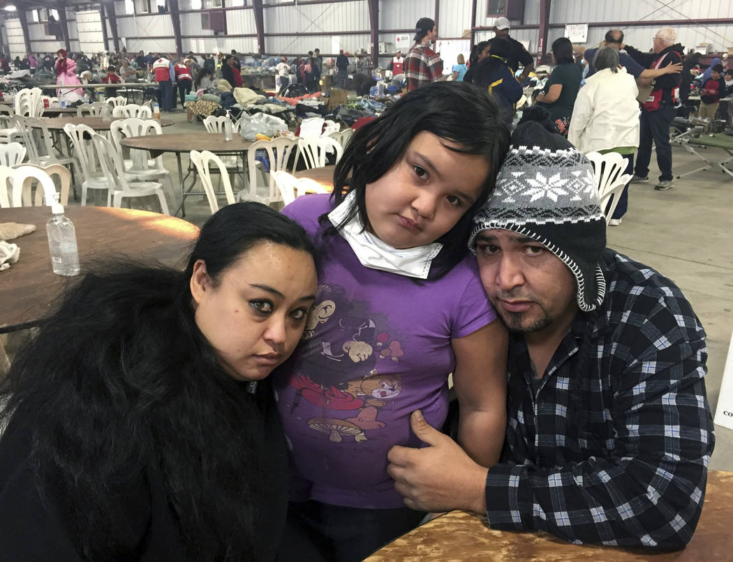 Wildfire survivors, Marolyn Romero-Sim, left, with Hugo Romero-Rodriguez, center, and their 9-year-old daughter, Milagros, sit inside the evacuation center at the Ventura County Fairgrounds in Ven ...