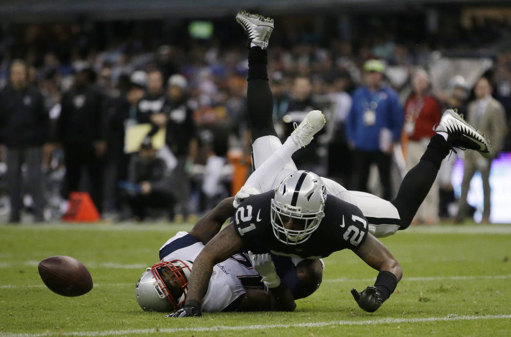 Oakland Raiders cornerback Sean Smith (21) breaks up a pass intended for New England Patriots wide receiver Brandin Cooks, left, during the second half of an NFL football game Sunday, Nov. 19, 201 ...