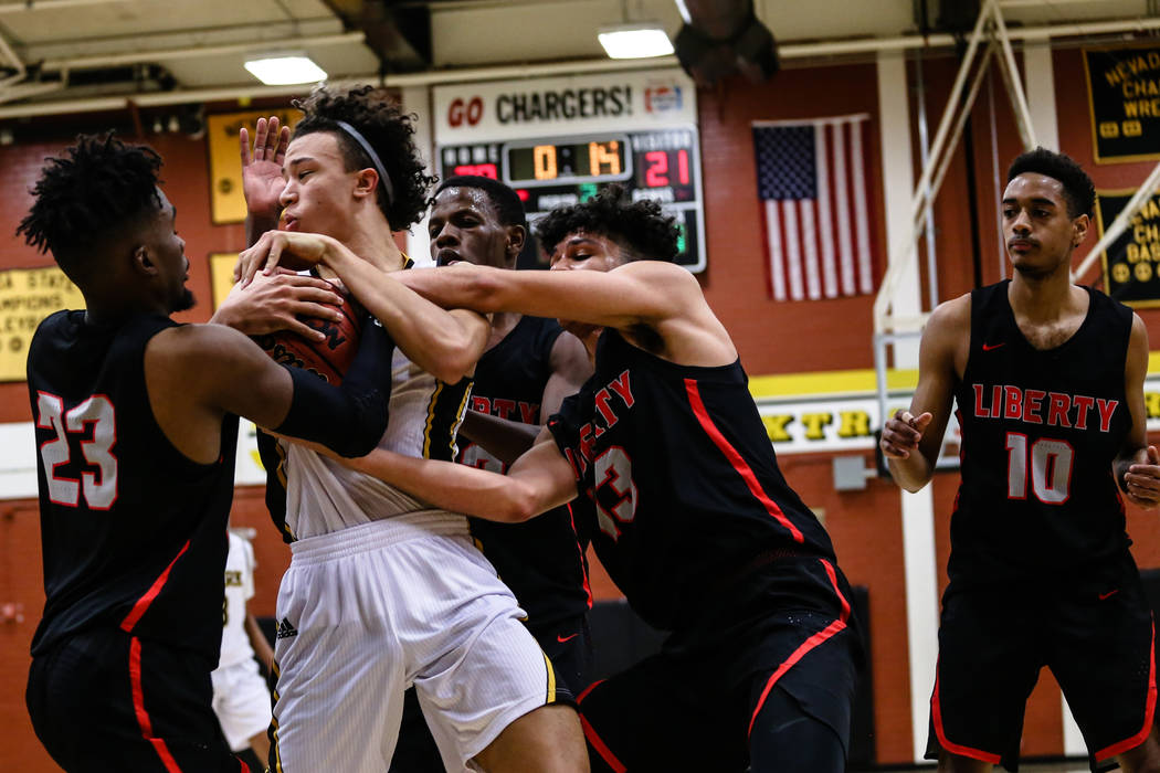Clark Chargers' Ian Alexander (32) holds the ball as players from Liberty attempt to grab it during the second quarter of a basketball game at Ed W. Clark High School in Las Vegas, Friday, Dec. 15 ...