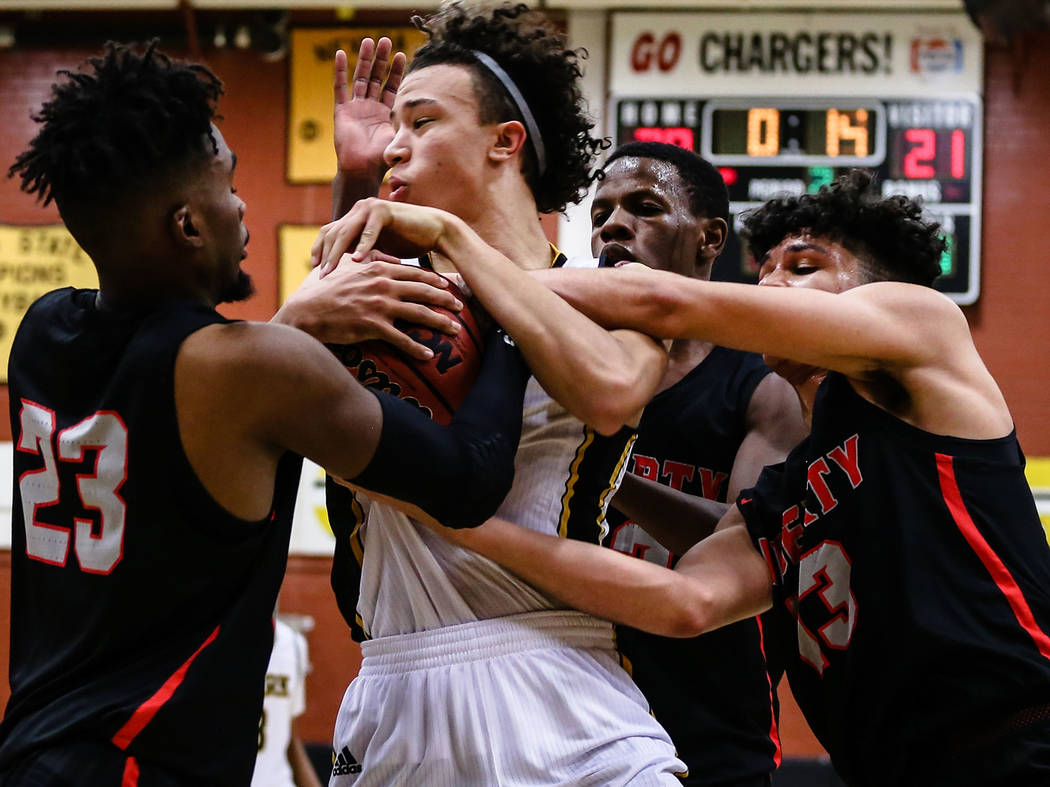 Clark Chargers' Ian Alexander (32) holds the ball as players from Liberty attempt to grab it during the second quarter of a basketball game at Ed W. Clark High School in Las Vegas, Friday, Dec.  ...
