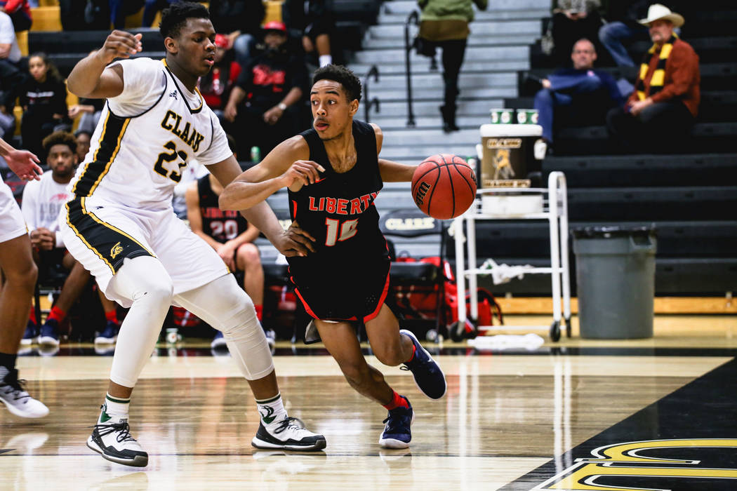 Clark Chargers' Antwon Jackson (23) guards Liberty's Jordan Holt (10) during the third quarter of a basketball game at Ed W. Clark High School in Las Vegas, Friday, Dec. 15, 2017. Clark Chargers w ...