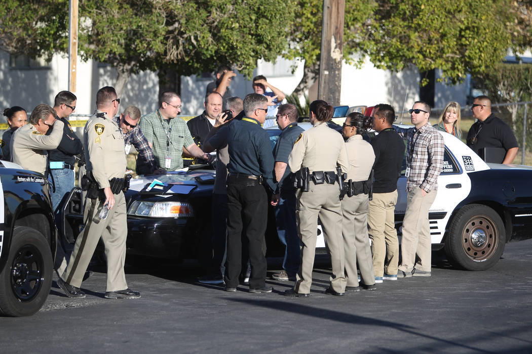 Las Vegas police investigate the scene at the corner of Holly Avenue and Allen Lane near Rancho and Vegas drives Friday, Dec. 1, 2017. A male shooting victim's body was found in the street 1900 bl ...