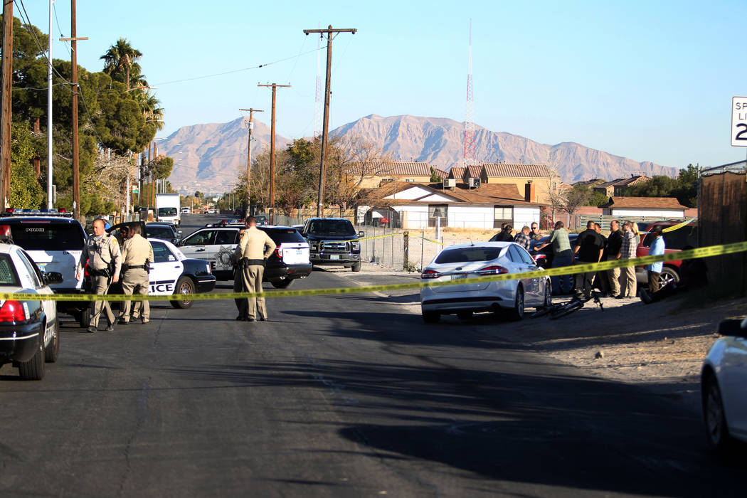 Las Vegas police investigate the scene at the corner of Holly Avenue and Allen Lane near Rancho and Vegas drives Friday, Dec. 1, 2017. A male shooting victim's body was found in the street. K.M. C ...