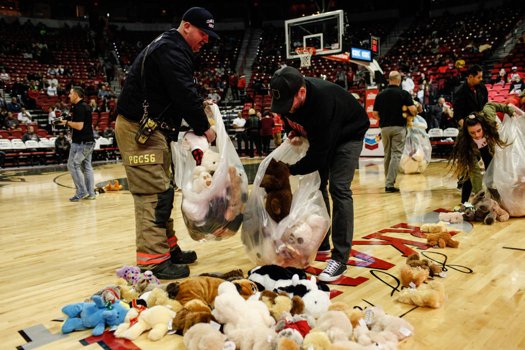Craig Vaccro of the Clark County Fire Department, 37, left, collects stuffed animals during the 2nd Annual Teddy Bear Toss during half-time of the UNLV Rebels and Mississippi Valley State Delta De ...