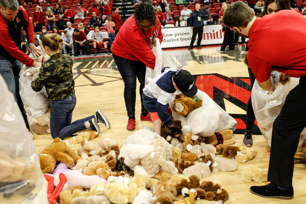 People gather stuffed animals during the 2nd Annual Teddy Bear Toss during half-time of the UNLV Rebels and Mississippi Valley State Delta Devils basketball game at the Thomas & Mack Center in ...