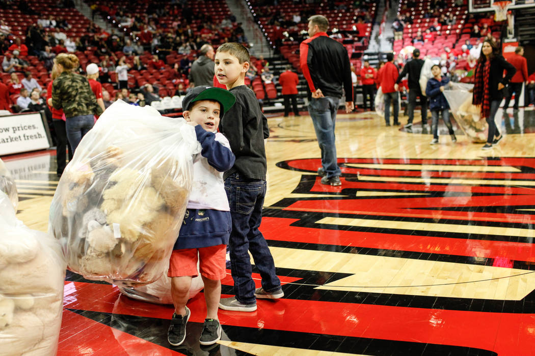 Austin Herrera of Henderson, 6, carries a bag full of stuffed animals during the 2nd Annual Teddy Bear Toss during half-time of the UNLV Rebels and Mississippi Valley State Delta Devils basketball ...