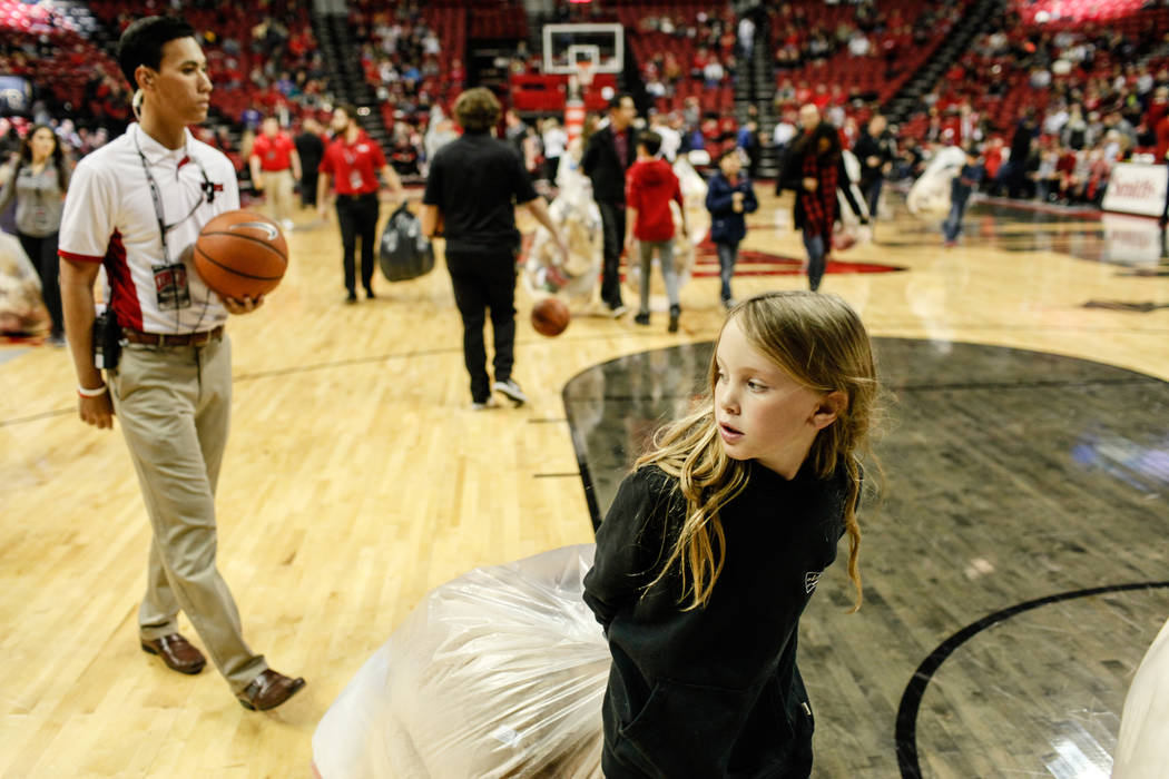 A child carries a bag full of stuffed animals during the 2nd Annual Teddy Bear Toss during half-time of the UNLV Rebels and Mississippi Valley State Delta Devils basketball game at the Thomas &amp ...