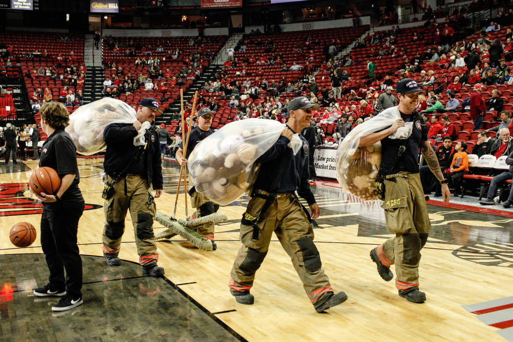 From left to right: Clark County Fire Department's Craig Vaccro, 37, Tyler Stacy, 33, Kevin Bialas, 44, and Jeremy Richmer, 38, carry bags full of stuffed animals during the 2nd Annual Teddy Bear  ...