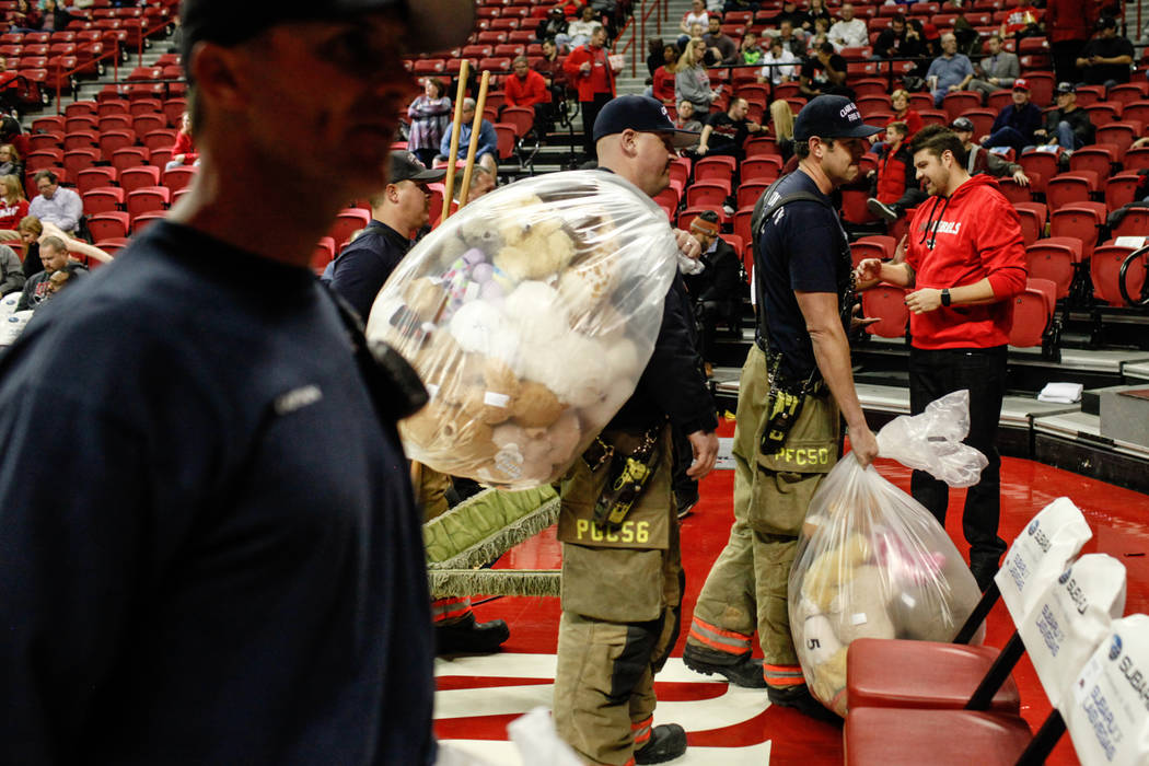 From left to right: Clark County Fire Department's Kevin Bialas, 44, Tyler Stacy, 33, Craig Vaccro, 37, and Jeremy Richmer, 38, carry bags full of stuffed animals during the 2nd Annual Teddy Bear  ...