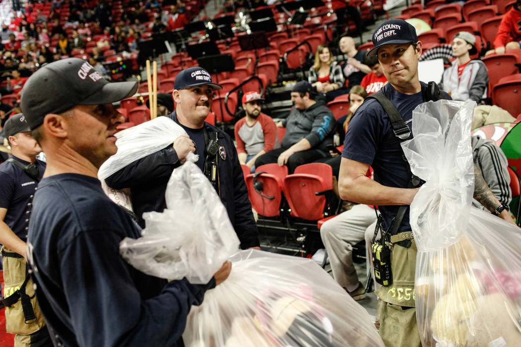 From left to right: Clark County Fire Department's Tyler Stacy, 33, Kevin Bialas, 44, Craig Vaccro, 37, and Jeremy Richmer, 38, carry bags full of stuffed animals during the 2nd Annual Teddy Bear  ...