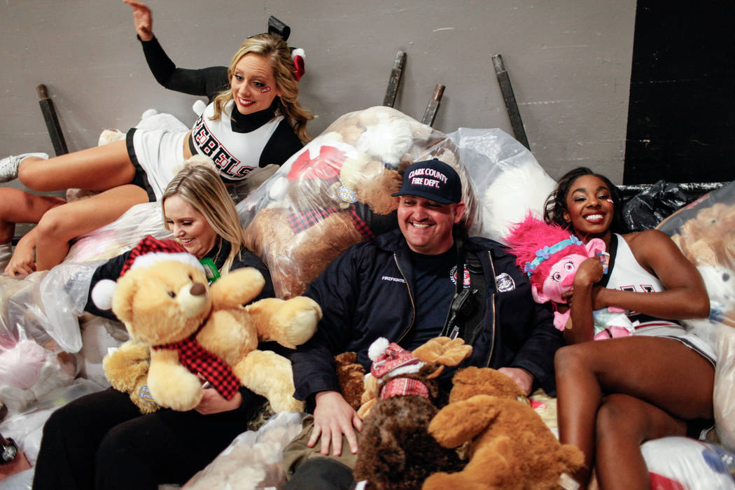 Clark County Fire Department's Craig Vaccro, 37, lies on bags full of stuffed animals during the 2nd Annual Teddy Bear Toss during half-time of the UNLV Rebels and Mississippi Valley State Delta D ...