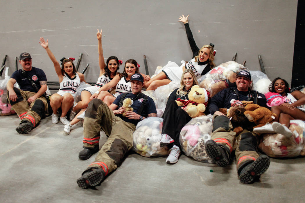 From left to right: Clark County Fire Department's Tyler Stacy, 33, Jeremy Richmer, 38, and Craig Vaccro, 37, gather with UNLV Rebels cheerleaders as then lean on bags full of stuffed animals duri ...