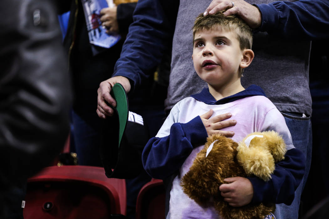Austin Herrera of Henderson, 6, places his hand over his heart during the national anthem as he holds a stuffed animal for the 2nd Annual Teddy Bear Toss at the UNLV Rebels and Mississippi Valley  ...
