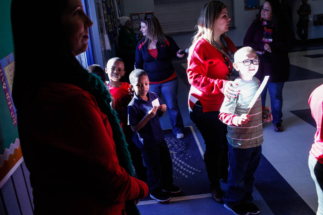 Students enter the cafeteria at C. T. Sewell Elementary School before receiving gifts donated by Bob and Sandy Ellis in Henderson, Friday, Dec. 22, 2017. This is the 13th year that the couple has  ...