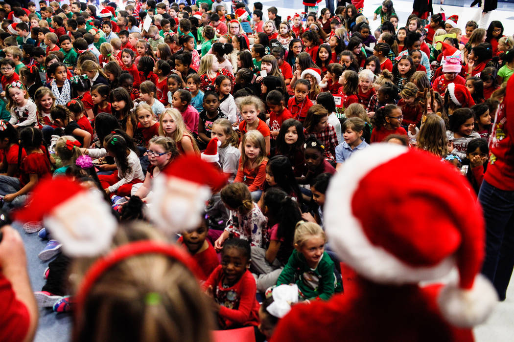 Students gather in the cafeteria at C. T. Sewell Elementary School as they wait to receive gifts donated by Bob and Sandy Ellis  in Henderson, Friday, Dec. 22, 2017. This is the 13th year that the ...