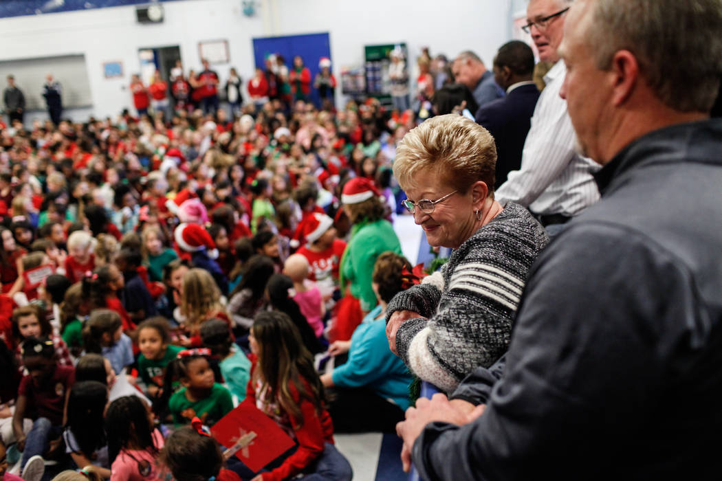 Sandy Ellis watches as students gather before handing them gifts at C. T. Sewell Elementary School in Henderson, Friday, Dec. 22, 2017. This is the 13th year that Sandy Ellis and her husband Bob E ...