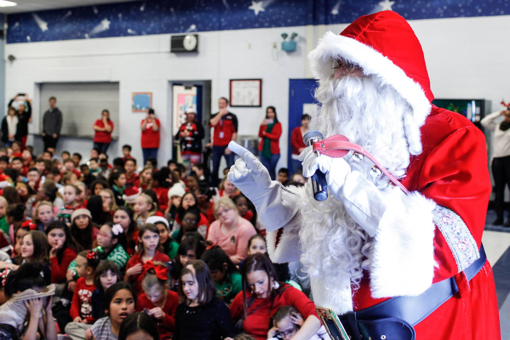 Students watch as Santa Claus speaks before handing out gifts donated by Bob and Sandy Ellis at C. T. Sewell Elementary School in Henderson, Friday, Dec. 22, 2017. This is the 13th year that the c ...