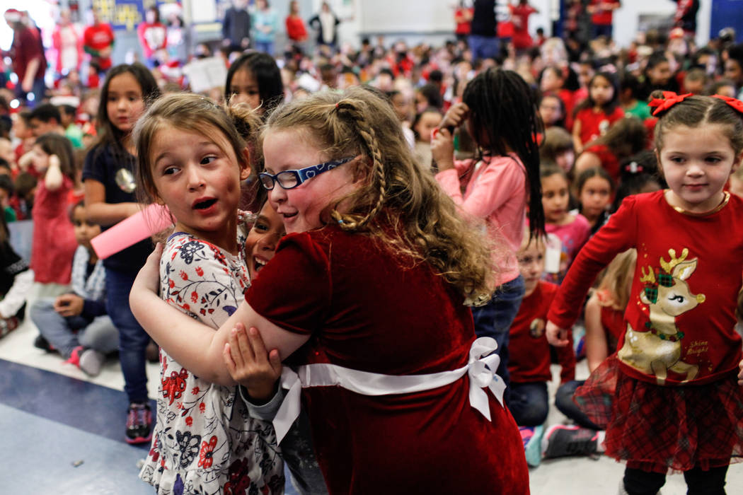 Kindergarten students Soleil Skalski, 5, left, Izabella Mendoza, 5, center, and Addison Wolf, 5, right, hug each other as donated gifts from Bob and Sandy Ellis are revealed at C. T. Sewell Elemen ...