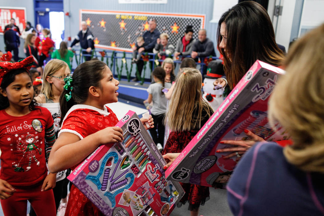 UNLV Athletic Director Desiree Reed-Francois hands out gifts donated by Bob and Sandy Ellis to students at C. T. Sewell Elementary School in Henderson, Friday, Dec. 22, 2017. This is the 13th year ...