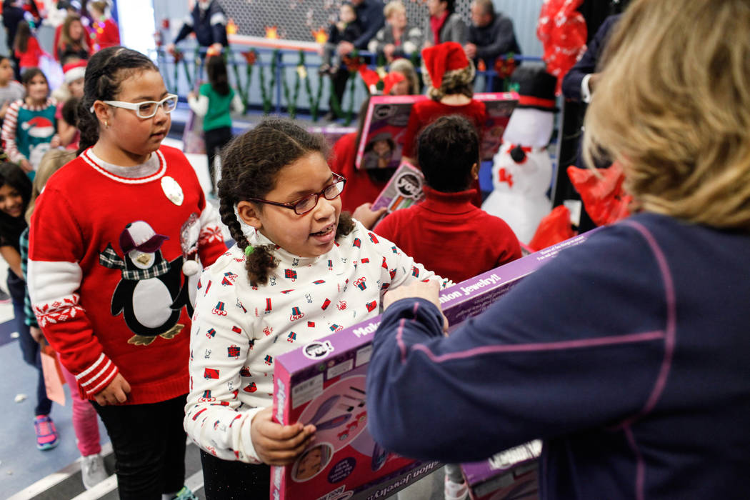 Students receive gifts donated by Bob and Sandy Ellis at C. T. Sewell Elementary School in Henderson, Friday, Dec. 22, 2017. This is the 13th year that the couple has donated gifts to underserved  ...