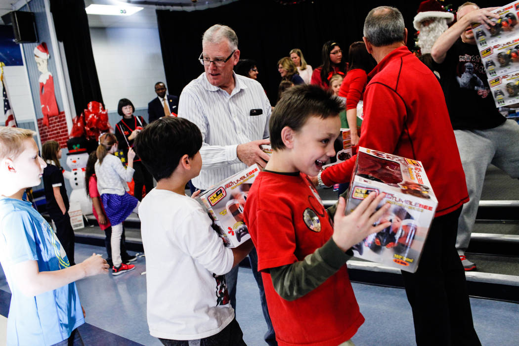 Former Henderson MayorAndy Hafen hands outgifts donated by Bob and Sandy Ellis to students at C. T. Sewell Elementary School in Henderson, Friday, Dec. 22, 2017. This is the 13th year  ...
