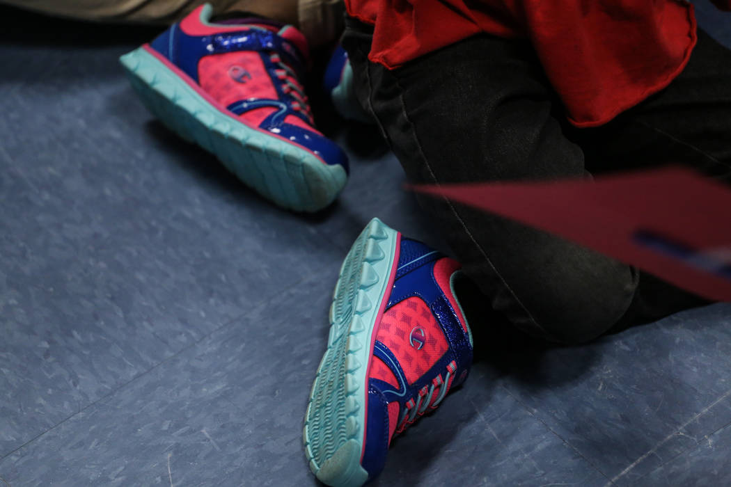 Students wear donated shoes from Bob and Sandy Ellis at C. T. Sewell Elementary School in Henderson, Friday, Dec. 22, 2017. This is the 13th year that the couple has donated gifts to underserved c ...