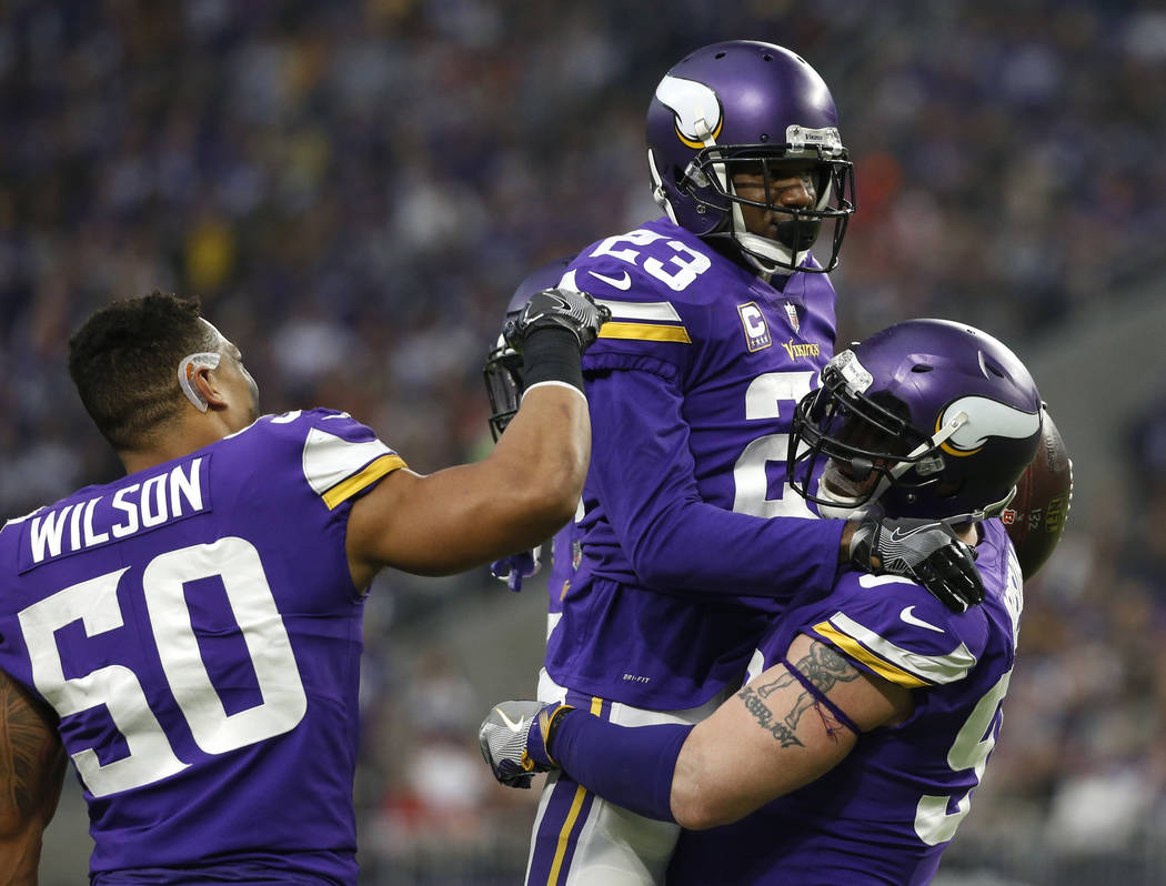 Minnesota Vikings cornerback Terence Newman (23) celebrates with teammates Brian Robison, right, and Eric Wilson (50) after intercepting a pass during the second half of an NFL football game again ...
