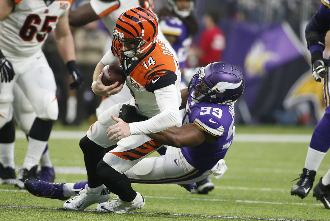 Cincinnati Bengals quarterback Andy Dalton (14) is sacked by Minnesota Vikings defensive end Danielle Hunter (99) during the first half of an NFL football game, Sunday, Dec. 17, 2017, in Minneapol ...