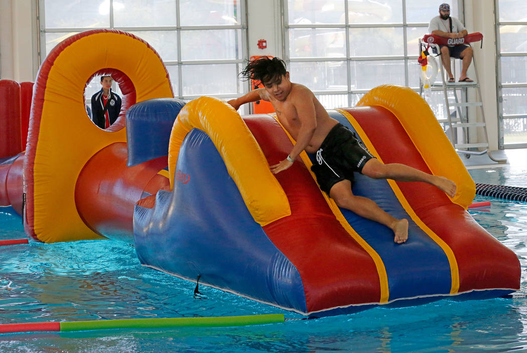 Lifeguard Reimart Yray, 19, of Las Vegas demonstrate playing on a water slide during the grand opening of 24,940-square-foot Aquatic Springs indoor pool in Las Vegas, Thursday, Dec. 21, 2017. Chit ...