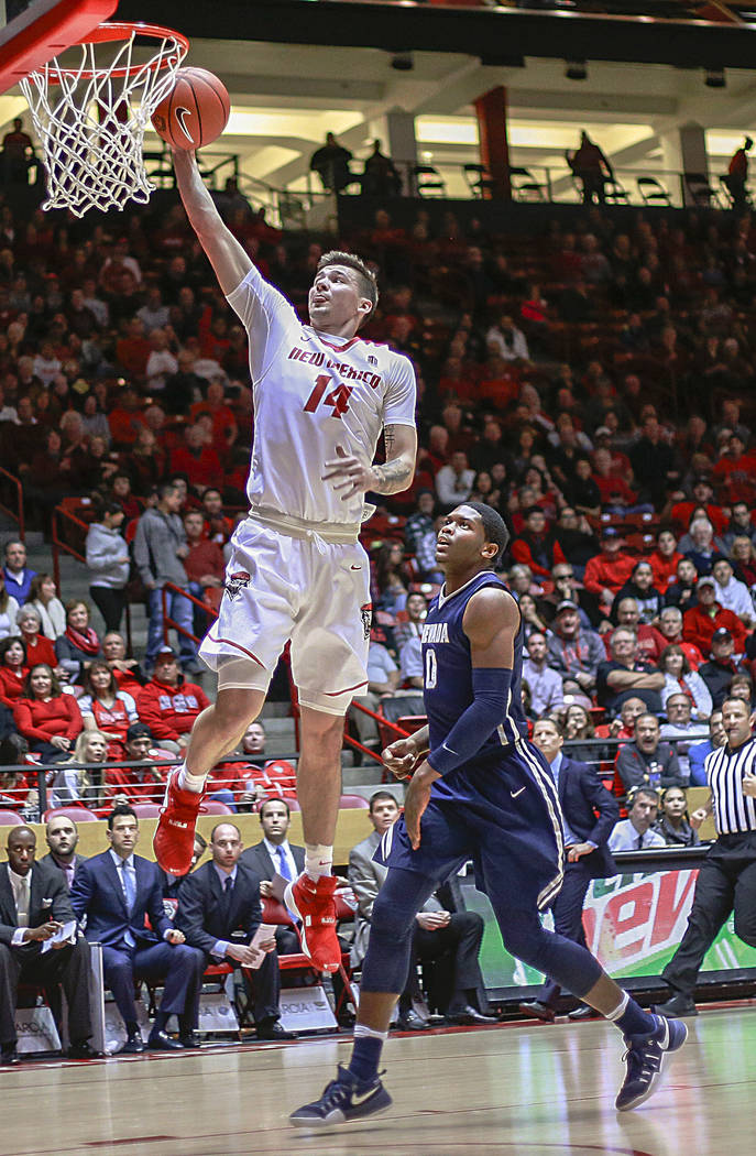 New Mexico's Dane Kuiper (14) dunks on a fast break trailed by Nevada's Cameron Oliver (0) during the first half of an NCAA college basketball game in Albuquerque, N.M., Saturday, Jan. 7, 2017. (A ...