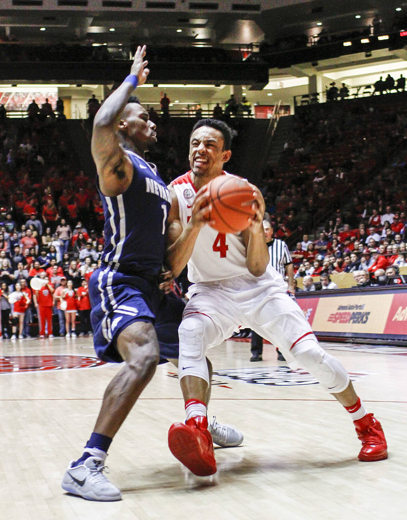 New Mexico's Elijah Brown (4) drives past Nevada's Marcus Marshall (1) during the second half of an NCAA college basketball game in Albuquerque, N.M., Saturday, Jan. 7, 2017. Nevada won in overtim ...
