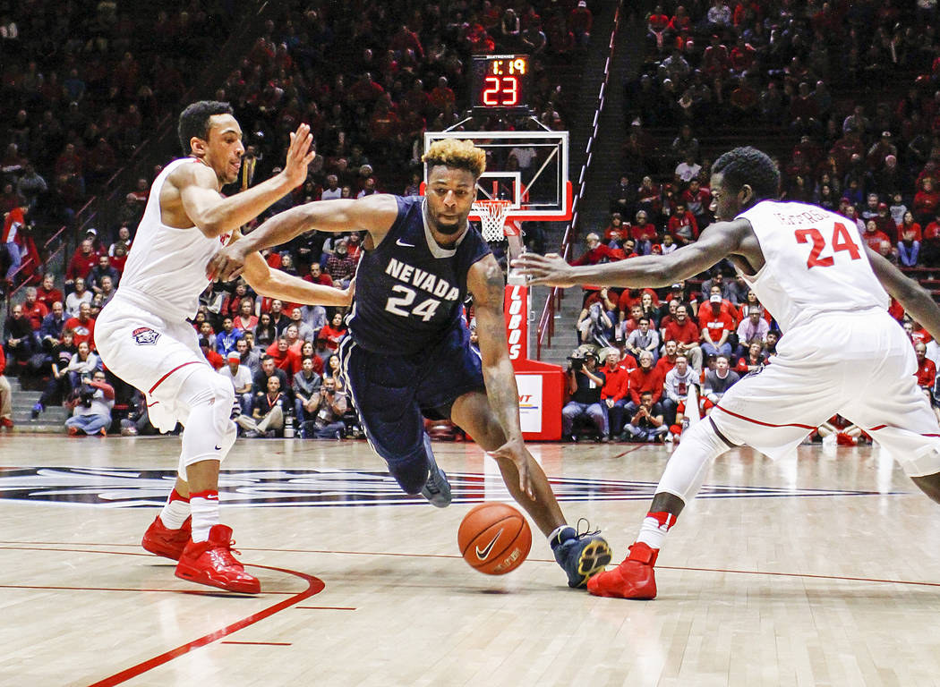 Nevada's Jordan Caroline (24) splits New Mexico's defense of Elijah Brown, left, and Damien Jefferson (24) during the second half of an NCAA college basketball game in Albuquerque, N.M., Saturday, ...