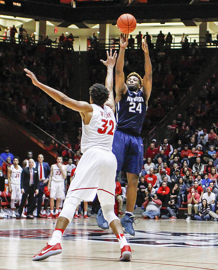 Nevada's Jordan Caroline (24) shoots a 3-pointer over New Mexico's Tim Williams (32) during the second half of an NCAA college basketball game in Albuquerque, N.M., Saturday, Jan. 7, 2017. Nevada  ...