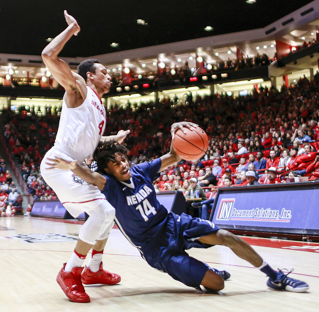 Nevada's Lindsey Drew (14) slips driving around New Mexico's Elijah Brown (4) during the second half of an NCAA college basketball game in Albuquerque, N.M., Saturday, Jan. 7, 2017. Nevada won in  ...