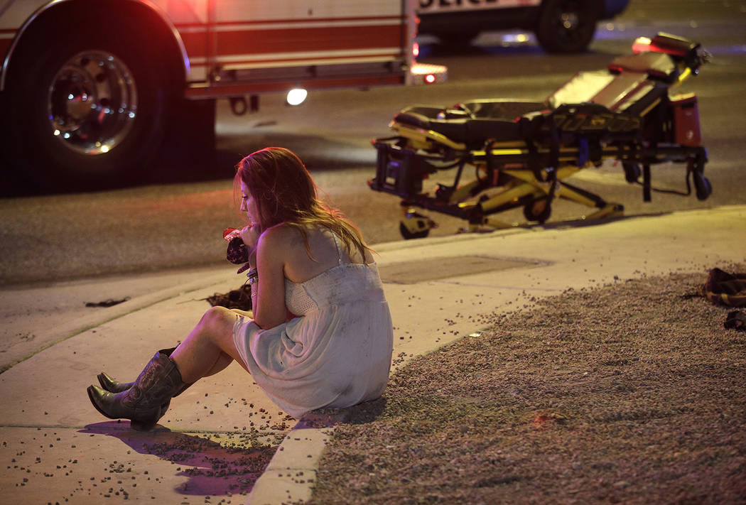 2017 AP YEAR END PHOTOS - A woman sits on a curb at the scene of a shooting outside a music festival on the Las Vegas Strip on Oct. 2, 2017. (AP Photo/John Locher)