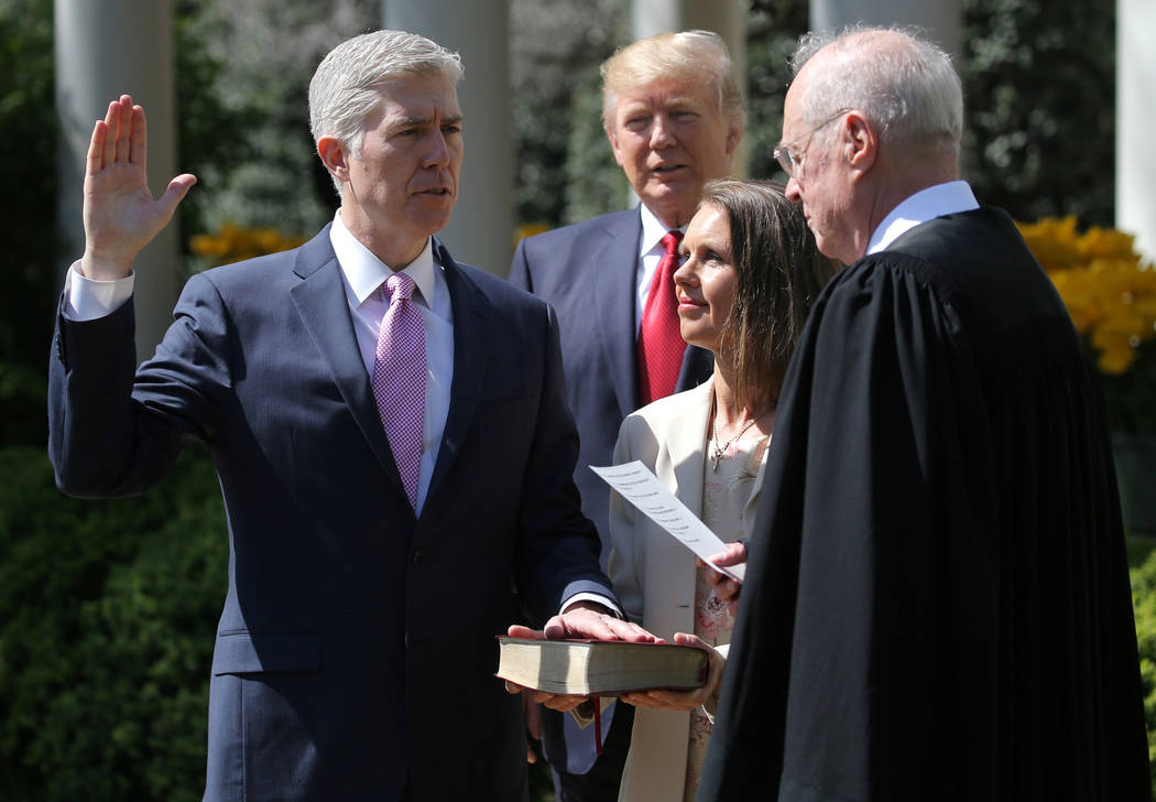FILE PHOTO: Judge Neil Gorsuch (L) is sworn in as an associate justice of the Supreme Court by Supreme Court Associate Justice Anthony Kennedy (R) , as U.S. President Donald J. Trump (C) watches w ...
