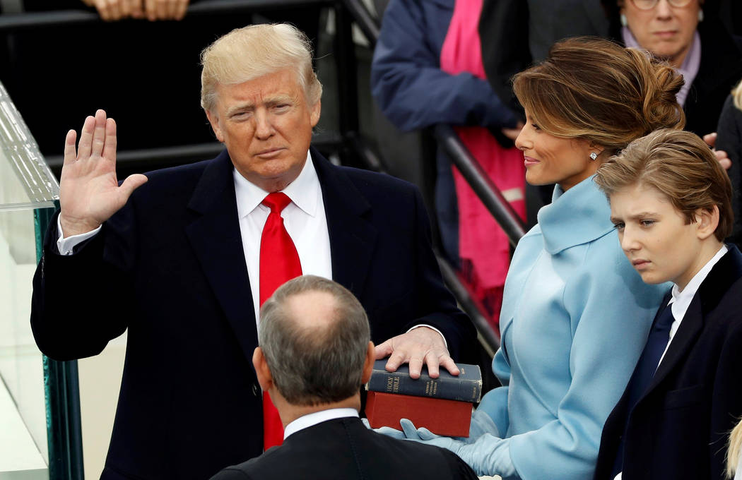 US President Donald Trump takes the oath of office with his wife Melania and son Barron at his side, during his inauguration at the U.S. Capitol in Washington, U.S., January 20, 2017. REUTERS/Kevi ...