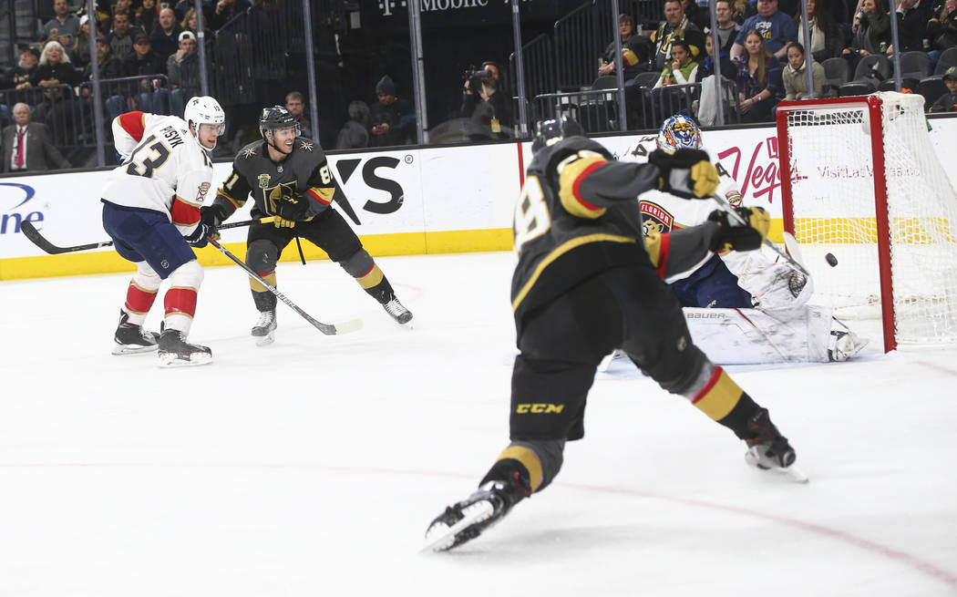 Golden Knights' Nate Schmidt (88) sends the puck in past Florida Panthers goalie James Reimer (34) against the Florida Panthers during an NHL hockey game at T-Mobile Arena in Las Vegas on Sunday,  ...