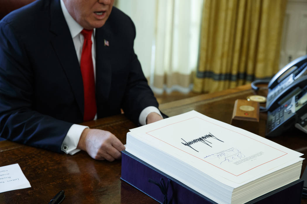 President Donald Trump speaks with reporters after signing the tax bill and continuing resolution to fund the government, in the Oval Office of the White House, Friday, Dec. 22, 2017, in Washingto ...