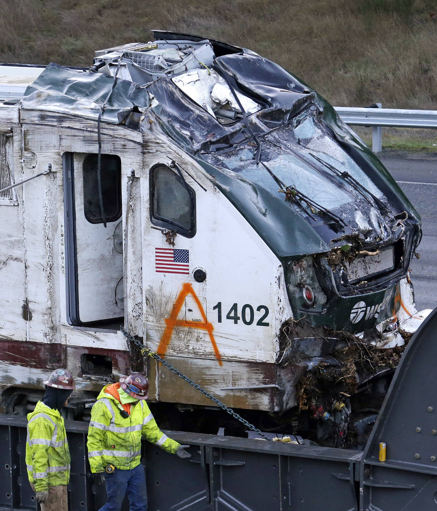 The engine from an Amtrak train crash onto Interstate 5 two days earlier is checked by workers before being transported away from the scene, Wednesday, Dec. 20, 2017, in DuPont, Wash. (AP Photo/El ...