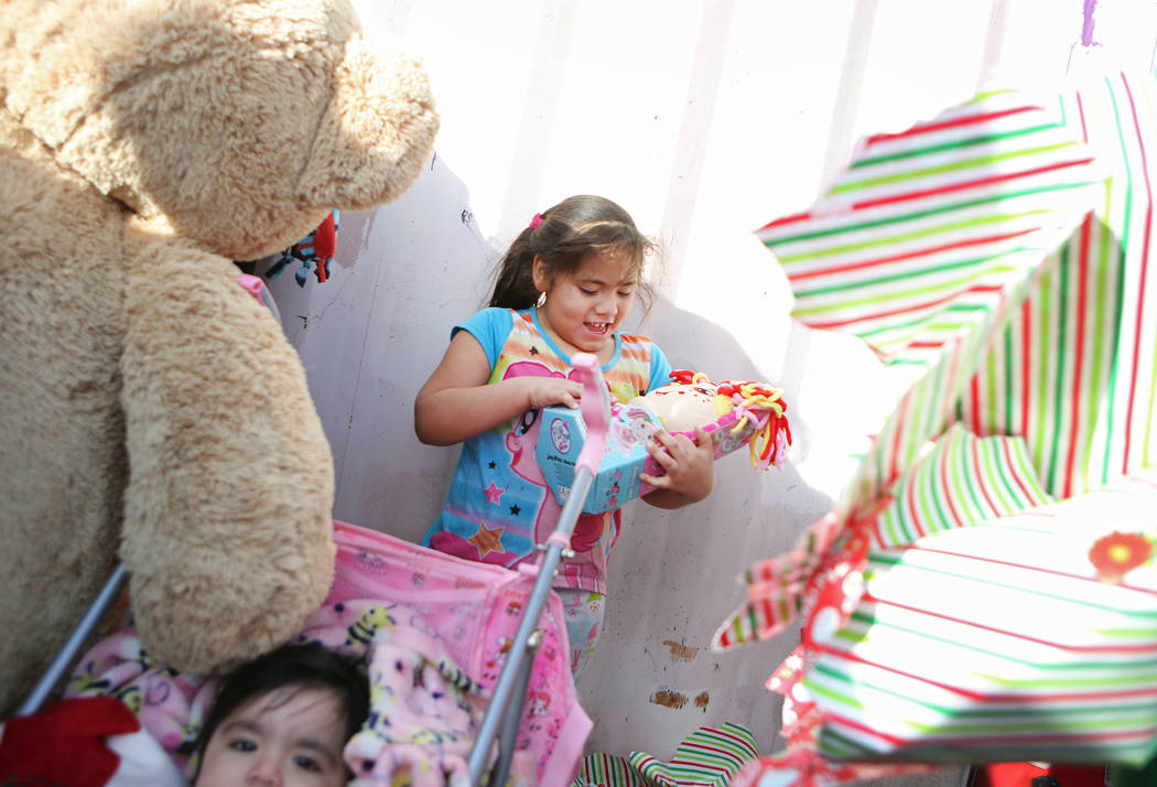 Ruby Hernandez, 5, looks at a toy she received outside her home, Sunday, Dec. 24, 2017, in North Las Vegas. North Las Vegas Fire Department emergency vehicles arrived with sirens blazing at Desert ...