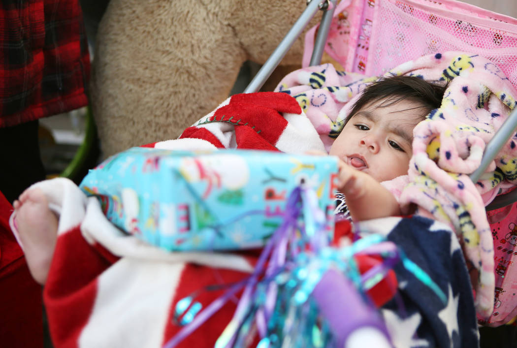 Isabella Hernandez, 7 months, plays with a present she received outside her home, Sunday, Dec. 24, 2017, in North Las Vegas. North Las Vegas Fire Department emergency vehicles arrived with sirens  ...