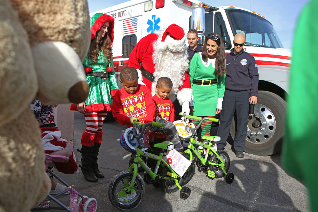 Terry Washington, 5, left, and brother Tyrese, 4, inspect their new bicycles near Santa Claus Sunday, Dec. 24, 2017, in North Las Vegas. North Las Vegas Fire Department emergency vehicles arrived  ...