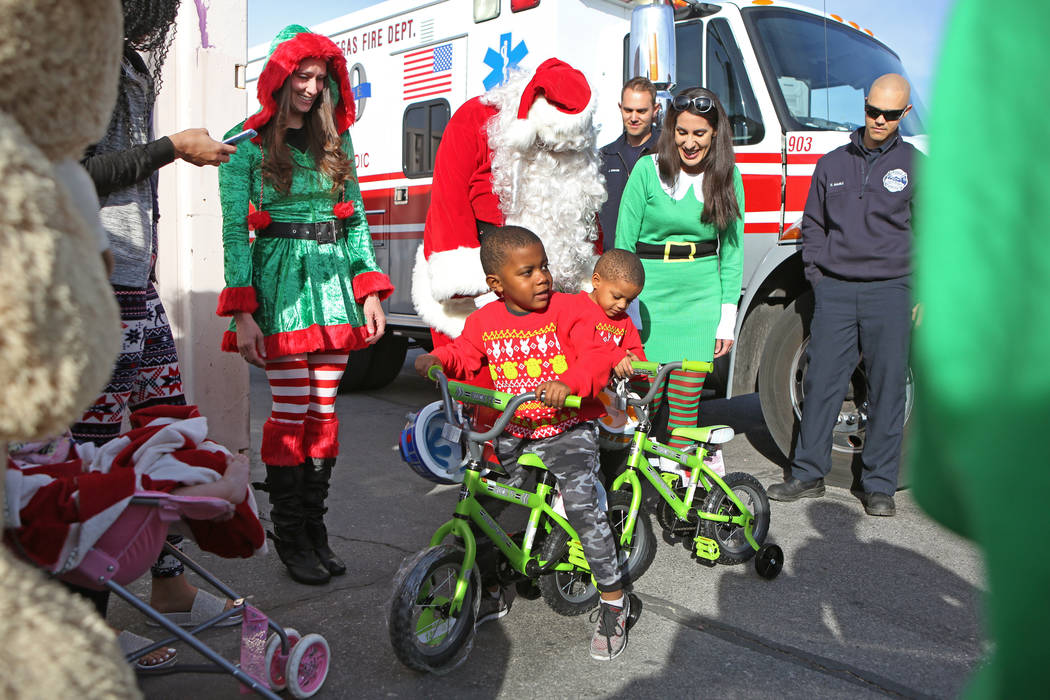Terry Washington, 5, left, and brother Tyrese, 4, interact with their new bicycles near Santa Claus, Sunday, Dec. 24, 2017, in North Las Vegas. North Las Vegas Fire Department emergency vehicles a ...