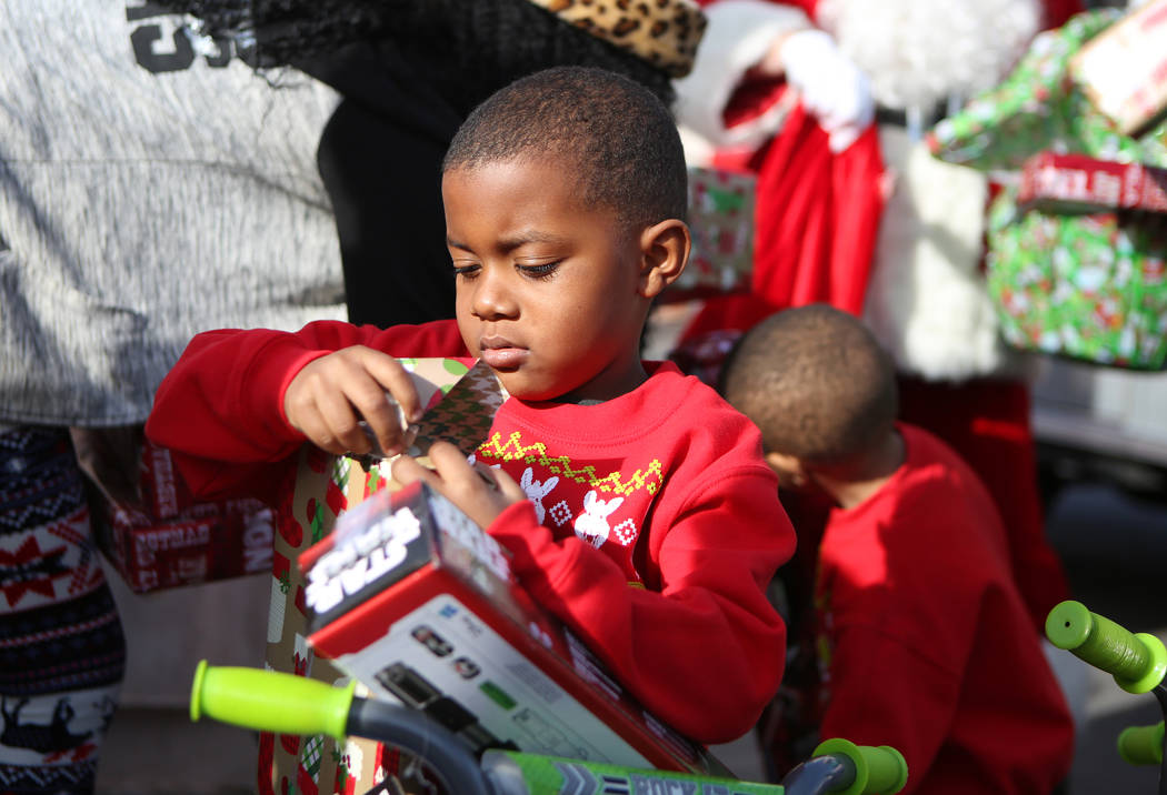 Terry Washington, 5, opens a gift he received outside his home, Sunday, Dec. 24, 2017, in North Las Vegas. North Las Vegas Fire Department emergency vehicles arrived with sirens blazing at Desert  ...