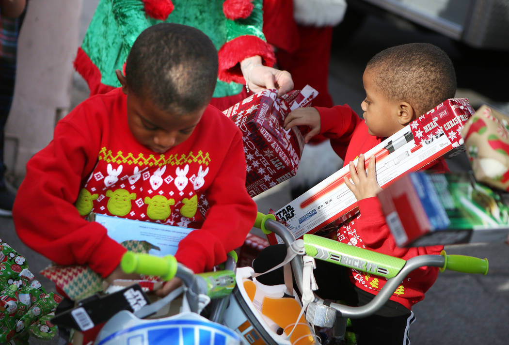 Terry Washington, 5, left, and brother Tyrese, 4, open gifts they received outside his home Sunday, Dec. 24, 2017, in North Las Vegas. North Las Vegas Fire Department emergency vehicles arrived wi ...
