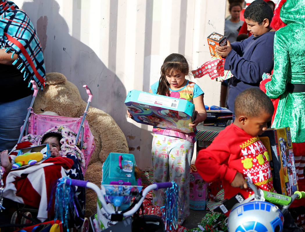 Ruby Hernandez, 5, center, looks at a toy she received outside her home, Sunday, Dec. 24, 2017, in North Las Vegas. North Las Vegas Fire Department emergency vehicles arrived with sirens blazing a ...