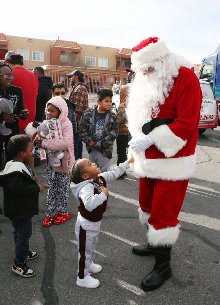Jase Bolen, 3, speaks to Santa Claus, Sunday, Dec. 24, 2017, in North Las Vegas. North Las Vegas Fire Department emergency vehicles arrived with sirens blazing at Desert Palms Apartments to surpri ...